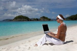 woman working on a laptop at a perfect beach in the caribbean